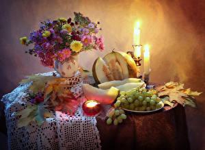 Фото Натюрморт Астры Свечи Виноград Дыни Стол Ваза Листья Продукты питания Цветы