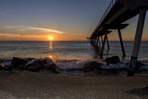 Фотография Испания Берег Рассветы и закаты Море Пирсы Волны Барселона Природа