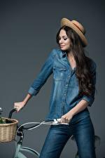 Картинки Велосипедный руль Серый фон Шляпы Джинсы Волосы Улыбается Брюнетки молодая женщина