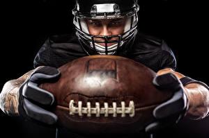 Фотографии Американский футбол Мужчины Черный фон Униформа Мяч Шлем Спорт