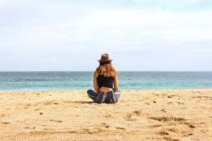 Картинки Пляж Песок Сидящие Шляпа Отдых Девушки