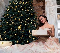 Картинка Новый год Новогодняя ёлка Подарки Шатенка Платье Сидящие Девушки