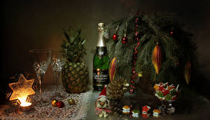 Картинки Новый год Натюрморт Сладкая еда Шампанское Ананасы Свечи Ветка Бутылка Бокалы Шар Снежинка Шишка