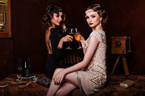 Фотографии Винтаж Вино Двое Бокалы Бутылки Платье Сидит Ноги молодые женщины