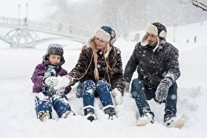 Картинки Зима Мужчина Снеге Мальчишка Шапки Сидящие Трое 3 Семья Дети Девушки