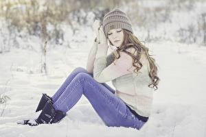 Фотографии Зимние Снег Шатенка Сидящие Шапки Ноги Джинсы Свитер Девушки