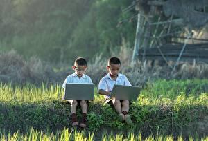 Фотографии Азиатка Мальчишка Траве Два Сидя Ноутбуки ребёнок