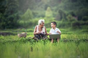Фотографии Азиаты Трава Мальчики Ноутбуки Сидит Вдвоем Старуха Дети