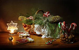 Картинки Рождество Свечи Печенье Сладости Орехи Натюрморт Стол Корзина На ветке Дизайн Банке Шар Пища