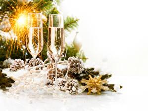 Фото Рождество Игристое вино Белый фон Шишки Бокалы Бенгальские огни Пища