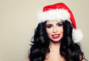 Картинка Рождество Цветной фон Брюнетка Шапки Смотрит Волосы Красные губы Девушки