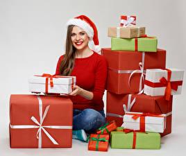 Обои Новый год Серый фон Шатенка Улыбка Шапки Подарки Сидящие Смотрит Девушки