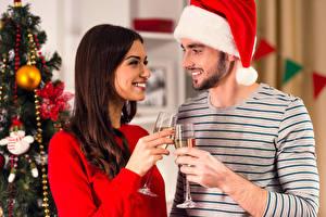 Картинка Новый год Мужчины Вино Двое Шатенка Улыбка Бокалы Шапки