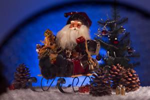 Фотографии Новый год Санта-Клаус Елка Санки Сидящие Подарки Шишки Борода Колокольчики