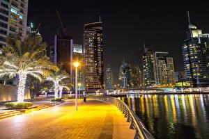 Фотография Дубай Объединённые Арабские Эмираты Здания Речка Уличные фонари Пальмы Ограда Ночные Набережная Города