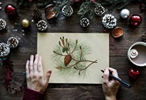 Картинка Пальцы Новый год Рука Лист бумаги Ветвь Шар Шишка