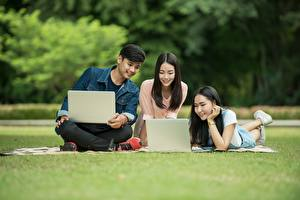 Фото Мужчины Студентки Сидящие Трава Втроем Брюнетка Ноутбуки Девушки