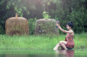 Фотографии Вода Азиаты Трава Брюнетка Сидящие Девушки