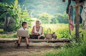 Фотография Азиатка Коты Мальчишки Старуха Корзина Сидящие Траве Ноутбук Дети