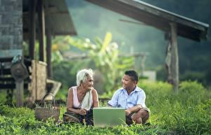 Фотография Азиаты Пожилая женщина Мальчик Сидит Траве Ноутбук Вдвоем ребёнок