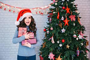 Картинка Новый год Шатенка Подарки Елка Шапки Руки Смотрит Девушки