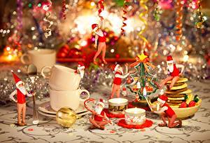Картинка Рождество Свечи Огонь Праздники Дед Мороз Шапка Сидит Чашка