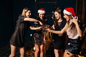 Картинки Рождество Игристое вино Шапки Платье Бокалы Радость Девушки