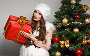 Картинка Рождество Новогодняя ёлка Шар Бантик Подарки Смотрит Шатенка Улыбка Шапки Девушки