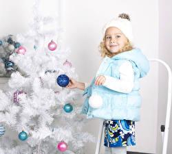Фотографии Рождество Новогодняя ёлка Шар Девочки Куртка Шапки Смотрит Ребёнок