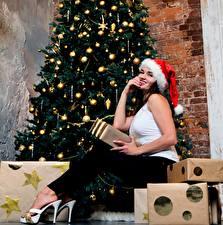Картинки Новый год Елка Подарков Шапки Шатенки Сидя Туфель Шарики девушка