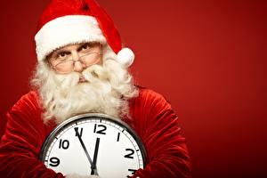 Картинки Рождество Часы Циферблат Красном фоне Шапки Очки Бородой Смотрит