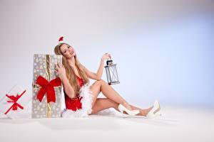 Обои Рождество Подарки Русые Униформа Сидит Шапки Бантик Лампа Ноги Туфли