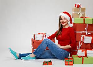 Обои Новый год Сером фоне Шатенка Подарков Взгляд Улыбается Шапки Джинсы Сидит девушка