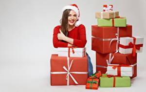 Картинки Новый год Серый фон Шатенка Улыбается Шапки Подарки девушка