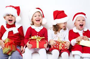 Картинка Рождество Девочки Мальчики Сидящие Подарки Бантик Шапки Счастье Смех Ребёнок