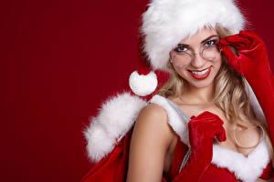 Картинки Рождество Красный фон Шапки Очки Взгляд Улыбка Девушки