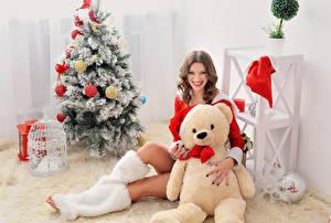 Фотографии Рождество Плюшевый мишка Шатенка Елка Улыбка Смотрит Сидящие Девушки
