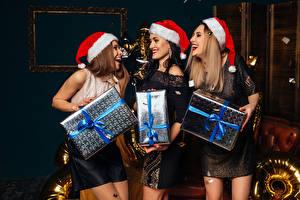 Фото Новый год Втроем Шапки Подарки Радость Девушки