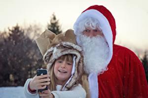 Картинка Рождество Зимние Дед Мороз Униформе Бородатые Девочка Вдвоем Селфи Смартфон Дети