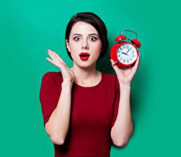 Фотография Часы Будильник Цветной фон Брюнетка Руки Эмоции изумление Девушки