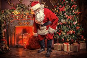 Фотографии Камин Новогодняя ёлка Подарки Санта-Клаус Бантик Шар Шапки Очки Борода Сапоги