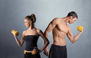 Фотография Фитнес Мужчина Сером фоне 2 Мускулы Гантеля Спорт