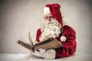 Фото Серый фон Санта-Клаус Книга Шапка Очках Бородатые Сидит