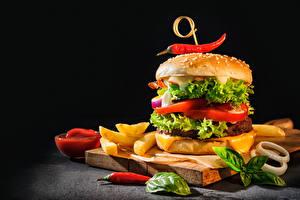 Фото Гамбургер Булочки Картофель фри Острый перец чили Овощи На черном фоне Разделочной доске Пища