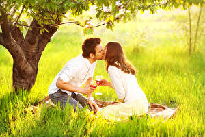 Картинка Мужчина Влюбленные пары Вино Траве Пикник Две Целование Бокалы Свидании Девушки