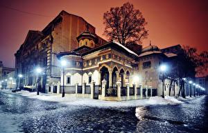 Картинка Румыния Здания Зимние Улица Ночные Уличные фонари Ограда Bucharest Города