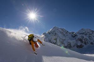 Фото Зимние Горы Лыжный спорт Мужчины Снегу Солнце Шлем спортивный