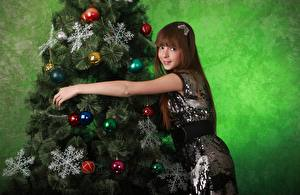 Картинки Рождество Елка Снежинки Шарики Шатенки Улыбается девушка