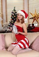 Картинки Рождество Новогодняя ёлка Диван Подарки Шапки Рыжая Смотрит Улыбка Девушки