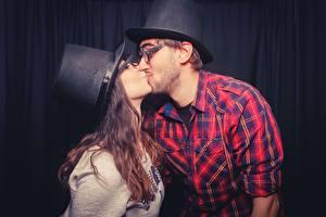 Картинки Влюбленные пары Мужчины 2 Поцелуй Шатенка Рубашка Очки Шляпа Девушки
